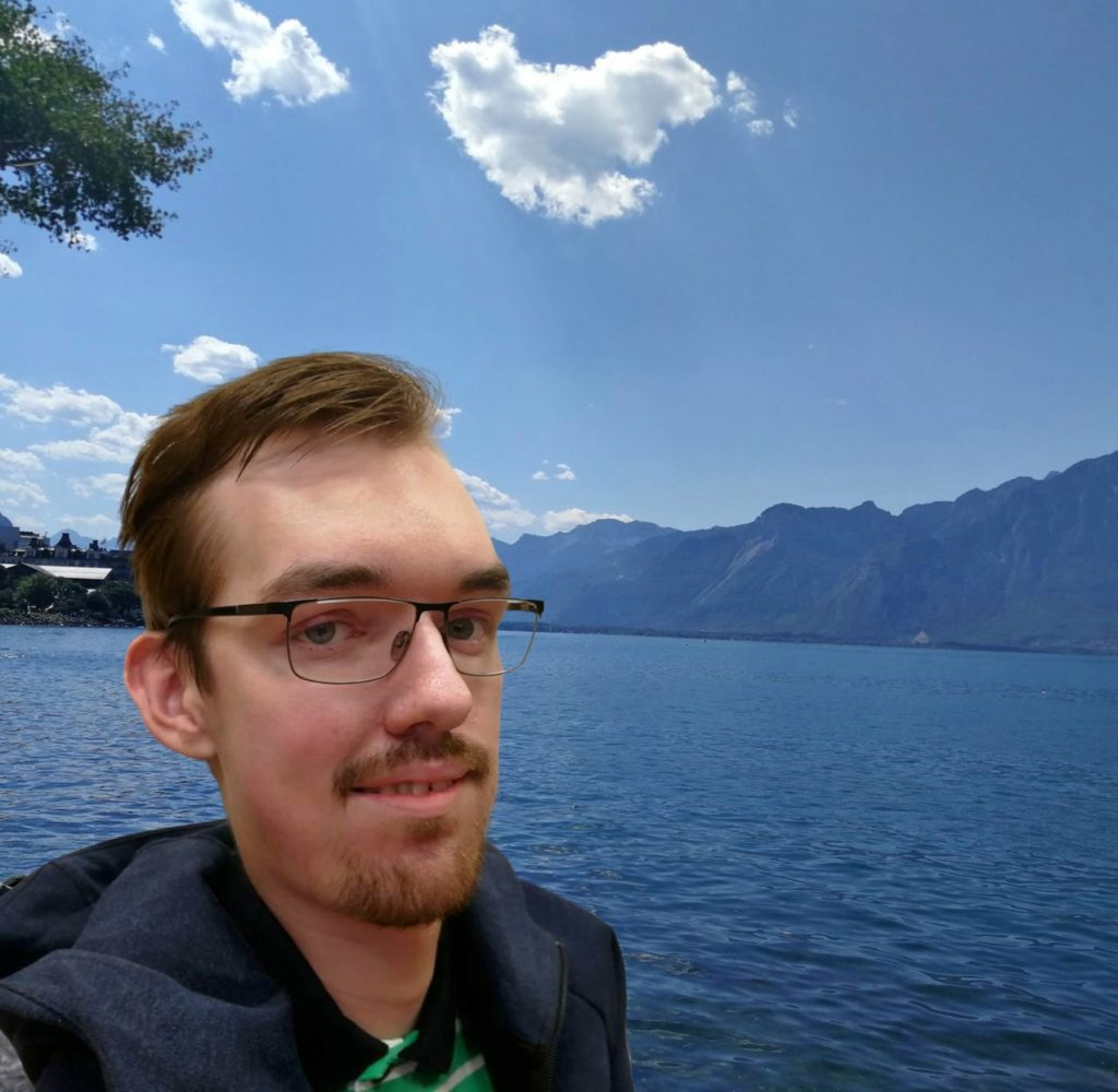 WordPress Engineer Aleksas Pantechovskis with a lake and mountains in the background