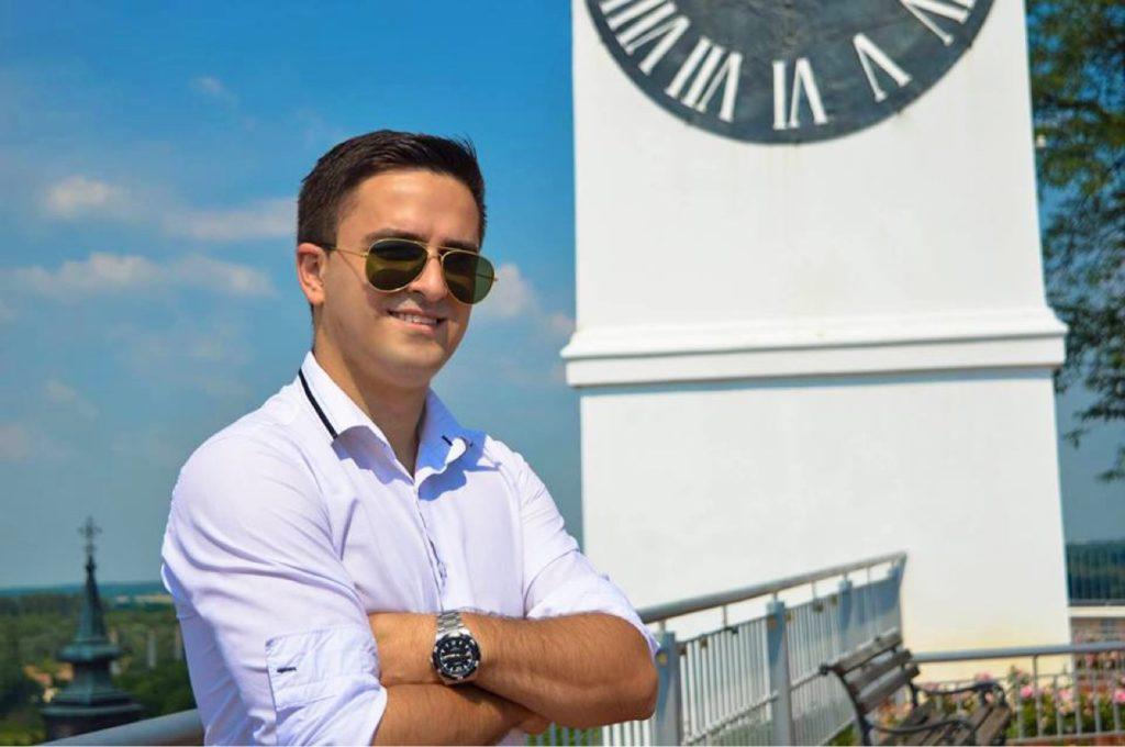 Inpsyder Aleš Fizešan an einem sonnigen Tag vor einer Turmuhr