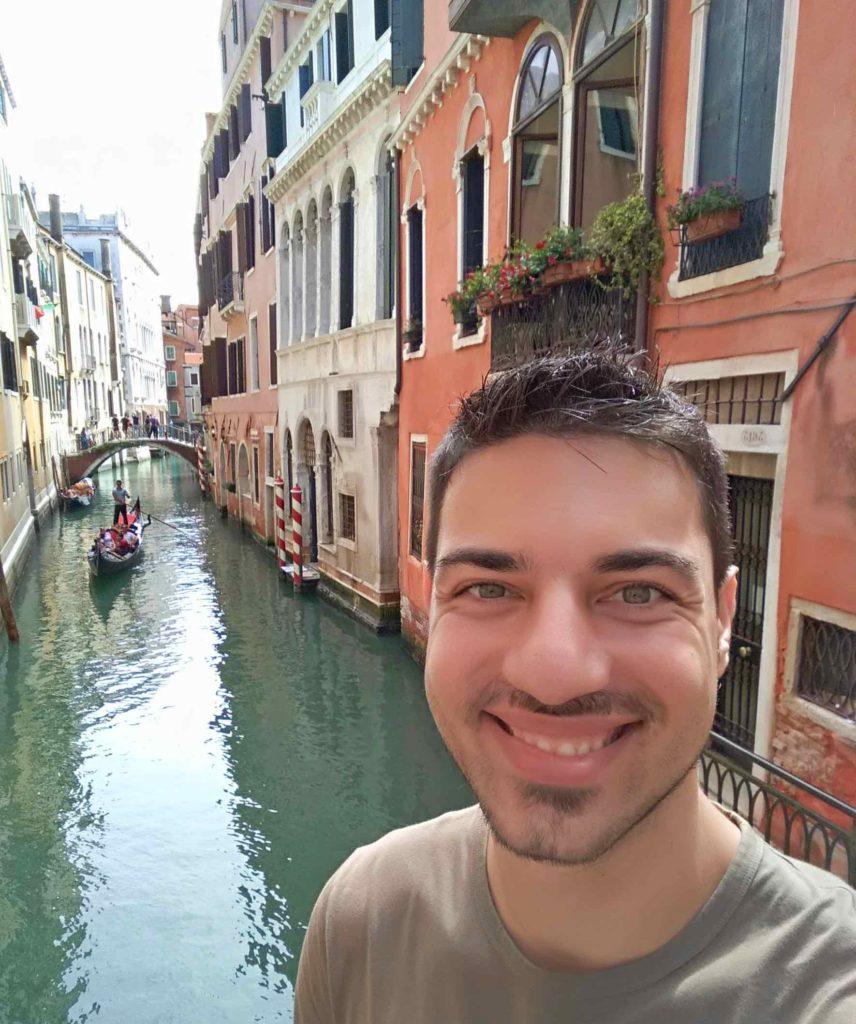 Orestis breit lächelnd, im Hintergrund ein venezianischer Kanal mit alten Häuserfassaden und einem Gondoliere.