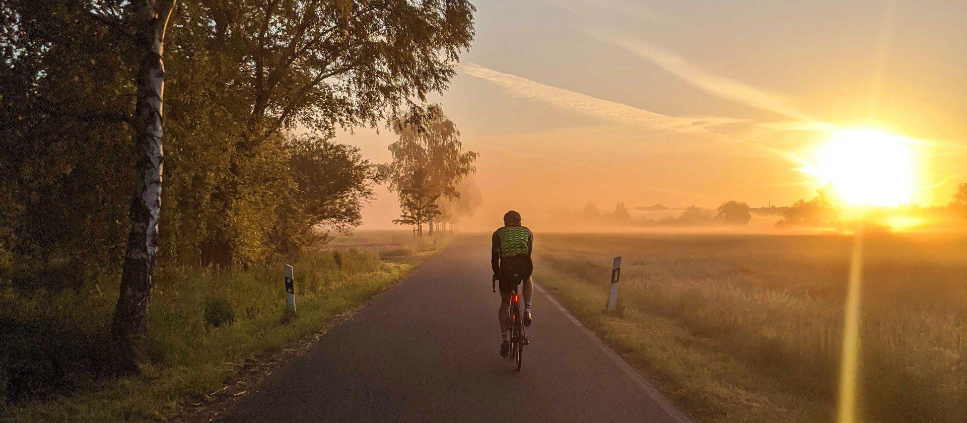 Frank Bültge fährt auf dem Fahrrad in den Sonnenuntergang