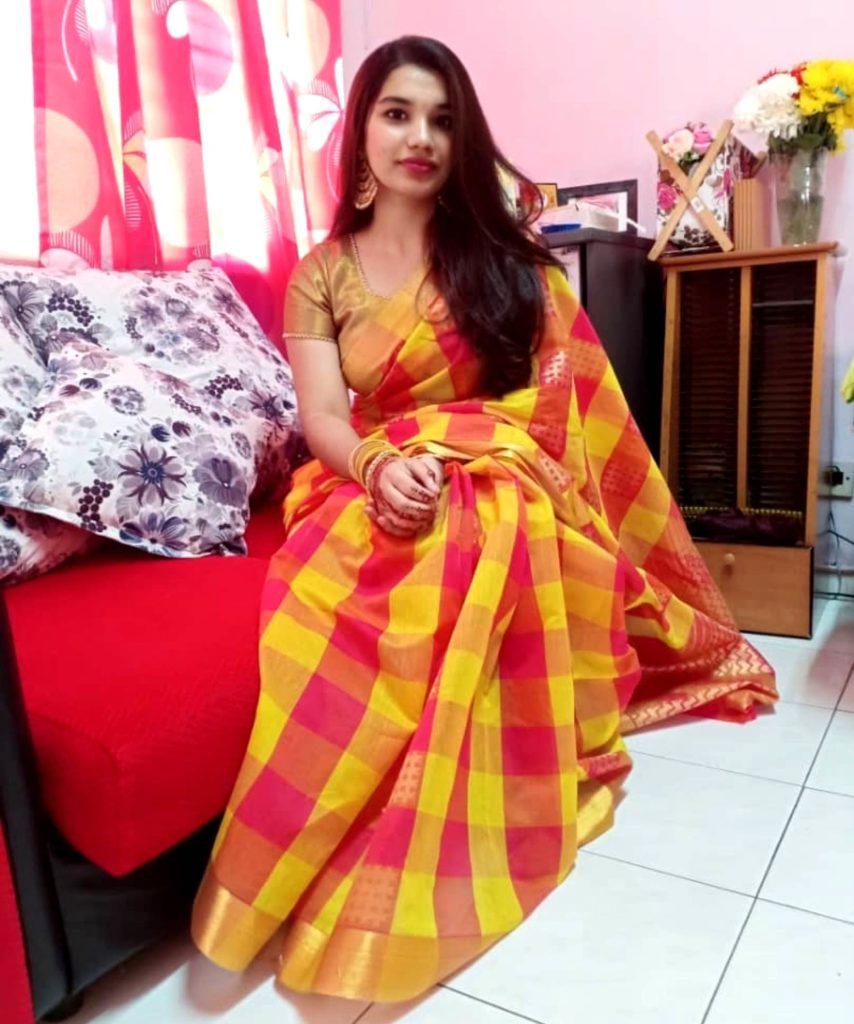 Yassviny sitzt lächelnd auf dem Sofa und trägt ein farbenfrohes indisches Saree mit großen Ohrringen und Armbändern.