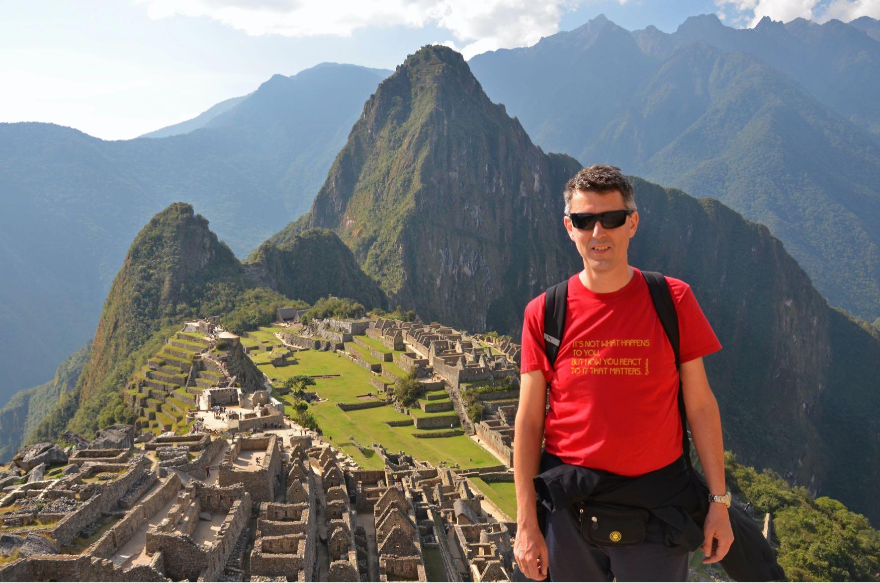 Auf diesem Bild steht Giancarlo mit Sonnebrille vor der Inka-Zitadelle von Machu Picchu, Peru.