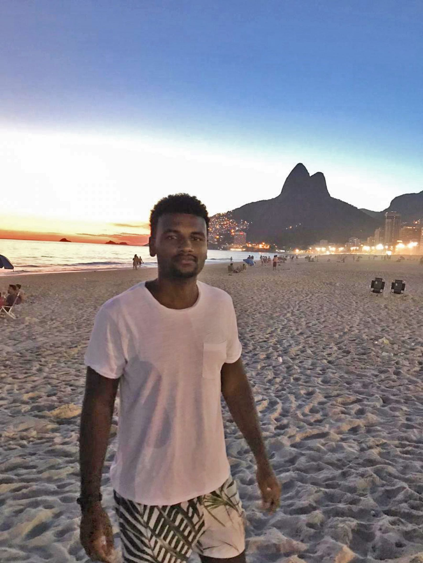 Das Bild zeigt Matheus bei Sonnenuntergang am Strand in Rio de Janeiro. Im Hintergrund sind die Lichter der Stadt zu sehen.