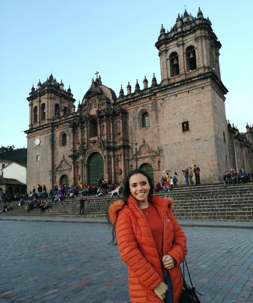 Auf dem Bild ist Liza in einem orangefarbenen Mantel zu sehen zu sehen, wie sie auf dem Plaza de Armas in Santiago de Chile vor der Kathedrale steht.