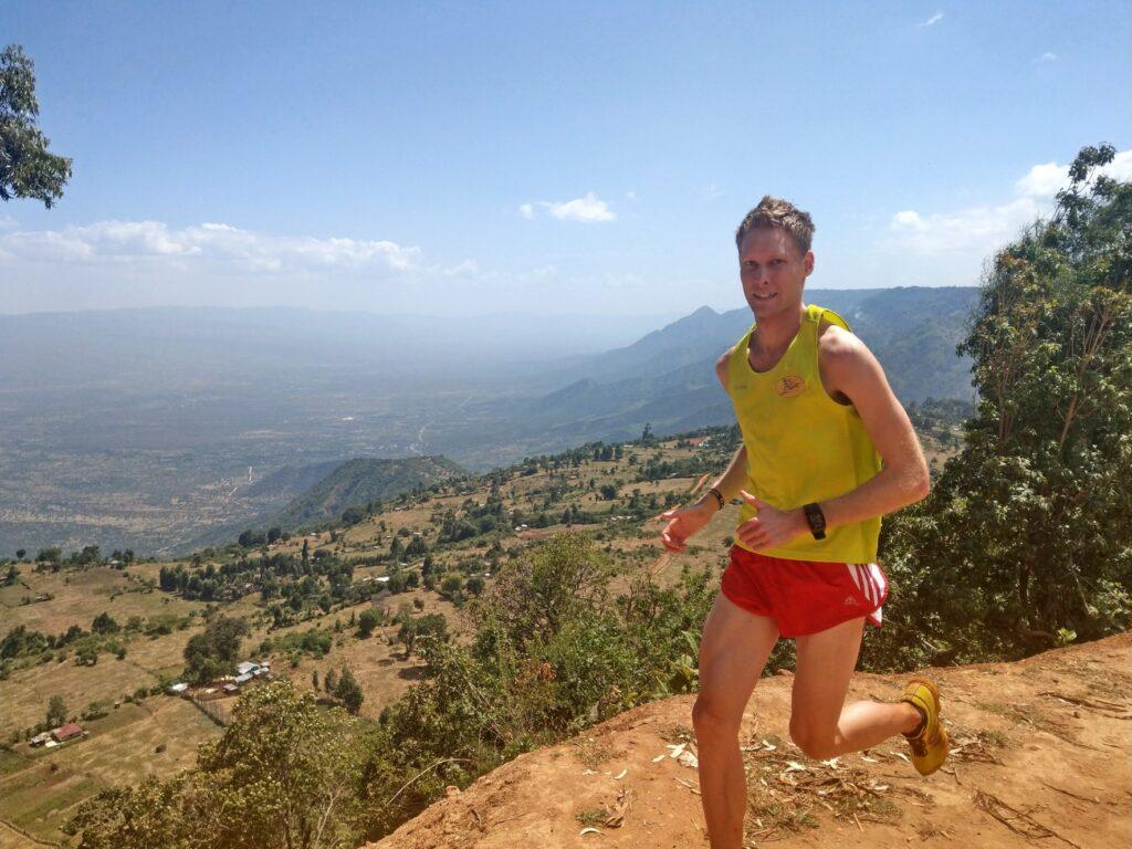 Auf dem Bild läuft Rico in Sportklamotten einen Weg entlang. Der Weg befindet sich in höheren Lagen, da sich im Hintergrund in ein Tal befindet.