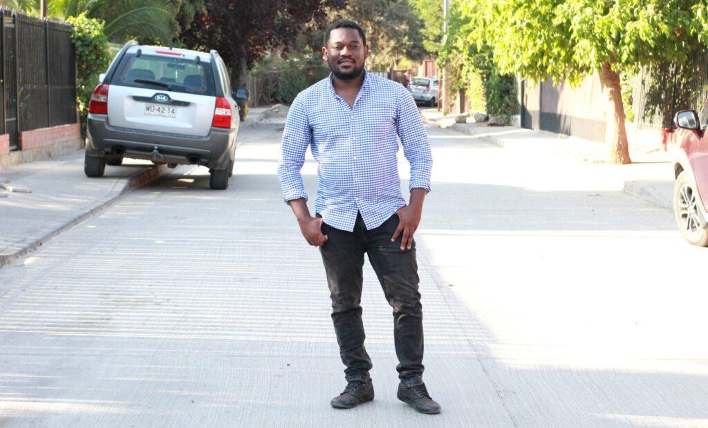 Auf dem Bild ist Sergot zu sehen wie er auf einer Straße steht, die Hände in den Hosentaschen trägt und in die Kamera schaut. Am rechten und linken Straßenrand stehen parkende Autos. Die Sonne scheint.