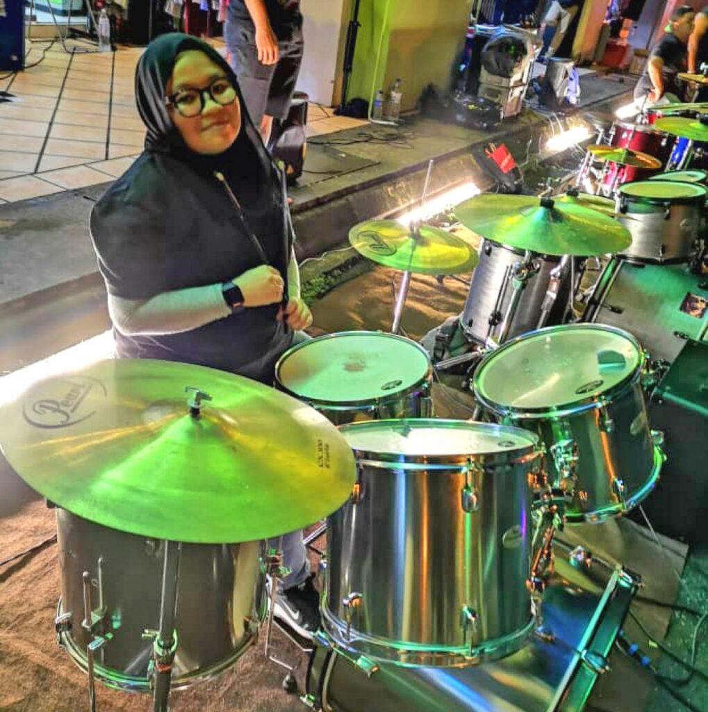 Das Bild zeigt Maya, wie sie Schlagzeug spielt.
