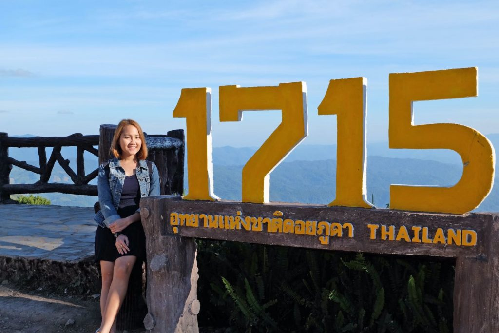 Judy at the 1715 viewpoint in Doi Phu Kha National Park in Thailand with a wide view of the landscape.