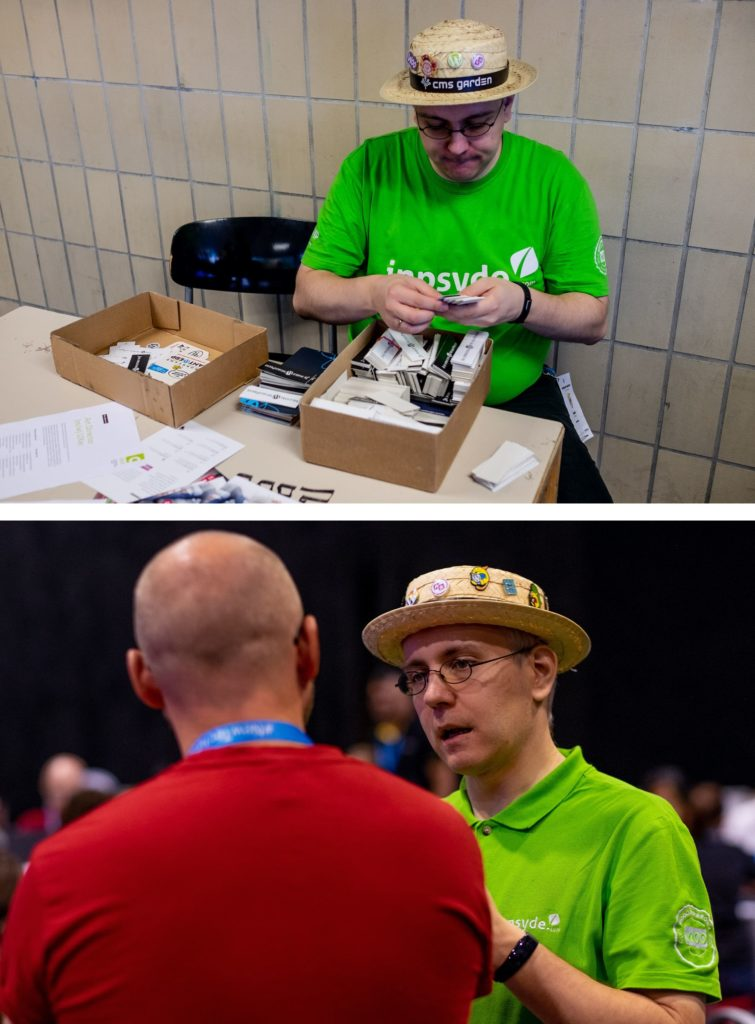 Robert in two photos: at a table at a WordCamp sorting stickers as presents and in a lively conversation with another man. On both photos, he wears his trademark, the straw hat with many patches.
