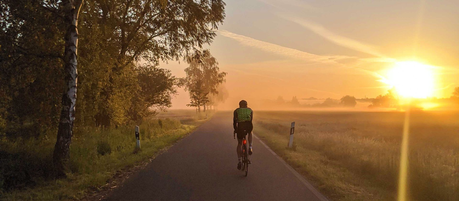 Frank Bültge rides on his bike into the sunset