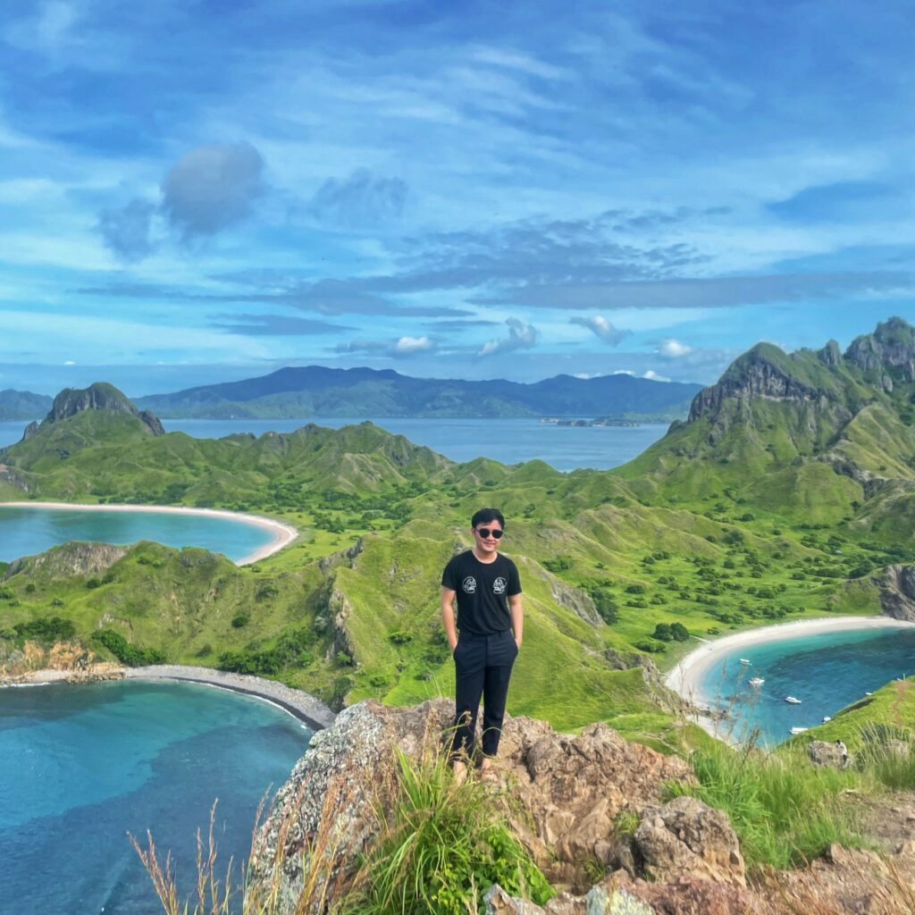 The picture shows Kevin visiting Labuan Bajo. He is standing on a cliff and behind him there are mountains and water.